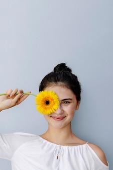 Bella ragazza con un fiore di gerbera gialla