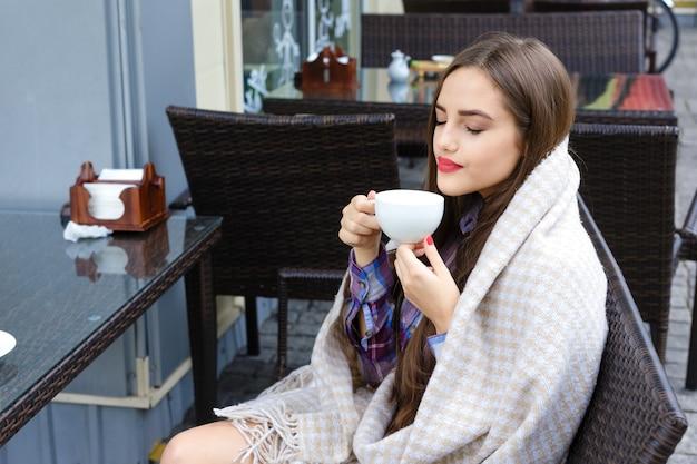 Bella ragazza avvolta in una coperta che tiene una tazza di tè in un caffè all'aperto