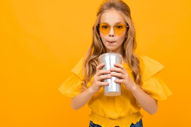 La bella ragazza in vestito giallo beve il succo su un fondo giallo