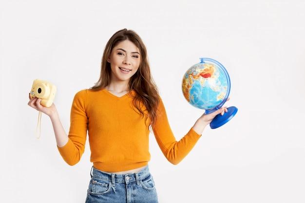 Una bella ragazza in un maglione giallo tiene in mano un globo e una macchina fotografica. ricreazione, viaggi, turismo. spazio per il testo