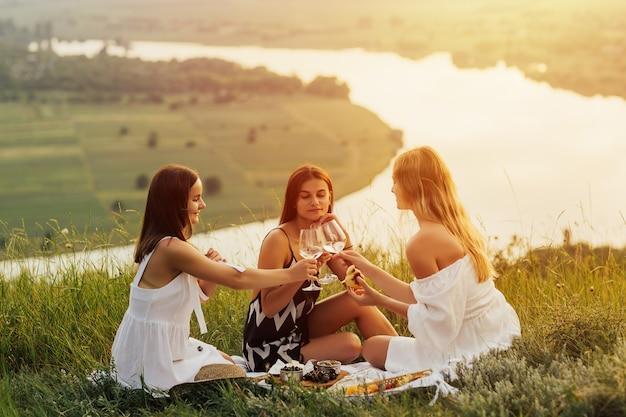 Amiche di belle ragazze giovani su un picnic in montagna in una giornata estiva.