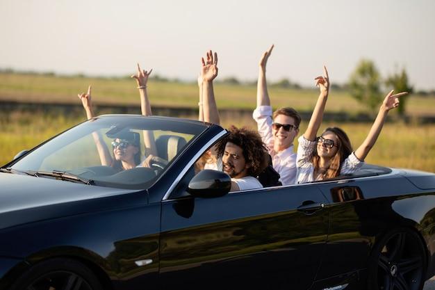 Belle ragazze e ragazzi in occhiali da sole sorridono e cavalcano in una cabriolet nera sulla strada alzando le mani in una giornata di sole. .