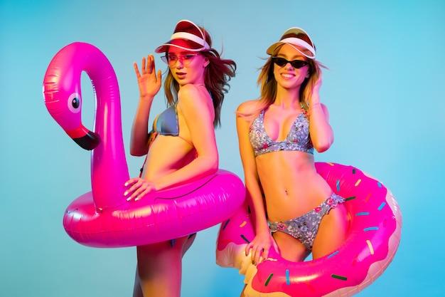 Ritratto a mezzo busto di belle ragazze isolato su sfondo blu studio in luce al neon. donne in posa in tuta alla moda. espressione facciale, estate, concetto di fine settimana. colori alla moda.