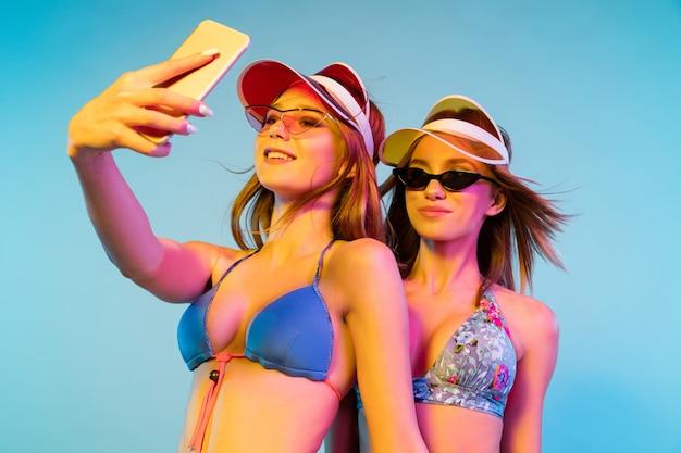 Ritratto a mezzo busto di belle ragazze isolato sulla parete blu alla luce al neon. donne in posa in tuta alla moda. espressione facciale, estate, concetto di fine settimana. colori alla moda.