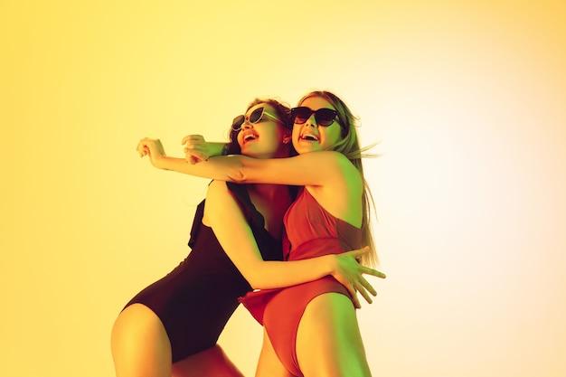 Ritratto di belle ragazze isolato su sfondo giallo studio in luce al neon. donne in tute alla moda. espressione facciale, estate, fine settimana, bellezza, concetto di resort. vacanze, gioventù.