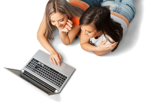Belle ragazze che usano il computer portatile durante la posa, isolate su bianco