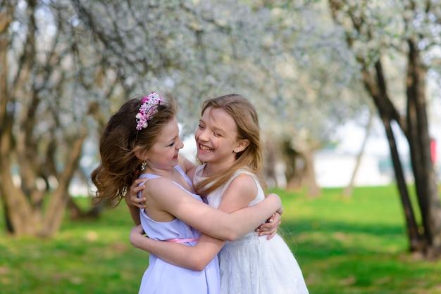 Belle ragazze giovani con gli occhi azzurri in abiti bianchi nel giardino con alberi di mele in fiore divertendosi e godendo l'odore del giardino fiorito primaverile.