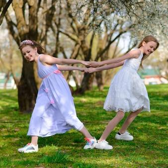 Belle ragazze con gli occhi azzurri in vestiti bianchi nel giardino con gli alberi di mele che sbocciano divertendosi e godendo dell'odore del giardino di fioritura della molla.