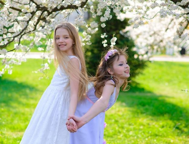 Belle ragazze con gli occhi azzurri in abiti bianchi in giardino con alberi di mele in fiore divertendosi