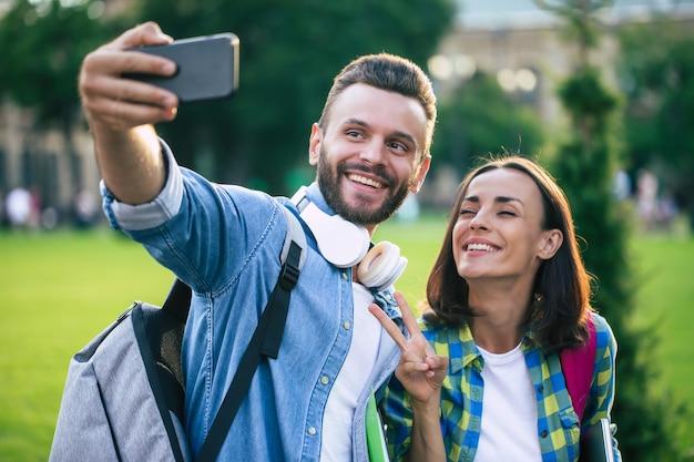 Belle giovani coppie felici in abiti casual con zaini stanno facendo selfie foto sullo smartphone