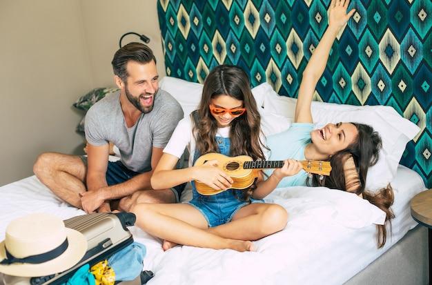 Bella giovane famiglia felice ed emozionata in una camera d'albergo di lusso durante il disimballaggio