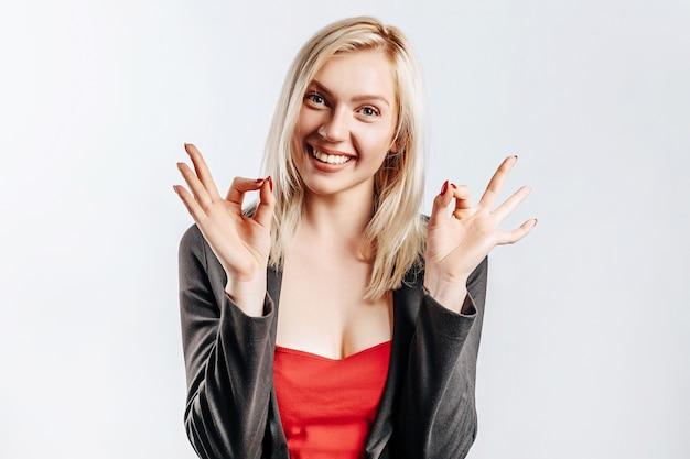 Bella giovane ragazza felice che mostra gesto giusto e sorridente su sfondo grigio isolato