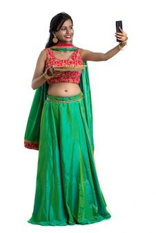 Bella giovane ragazza felice che prende un selfie con la lampada dell'argilla o il diya durante il festival di luce diwali facendo uso di uno smartphone su un bianco