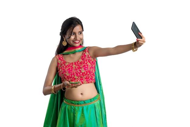 Bella giovane ragazza felice che cattura un selfie con lampada di argilla o diya durante il festival della luce diwali