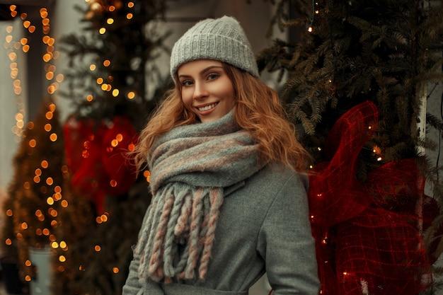 Bella giovane ragazza modello felice con un sorriso in un cappotto grigio elegante e un cappello vintage lavorato a maglia alla moda con una sciarpa che cammina in città in vacanza vicino alle luci dorate
