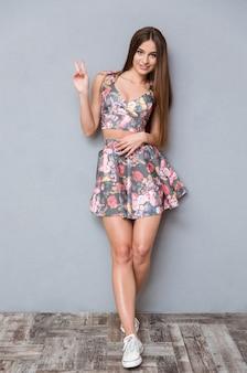 Bella giovane donna alla moda positiva sorridente felice che mostra il segno di pace e che sorride