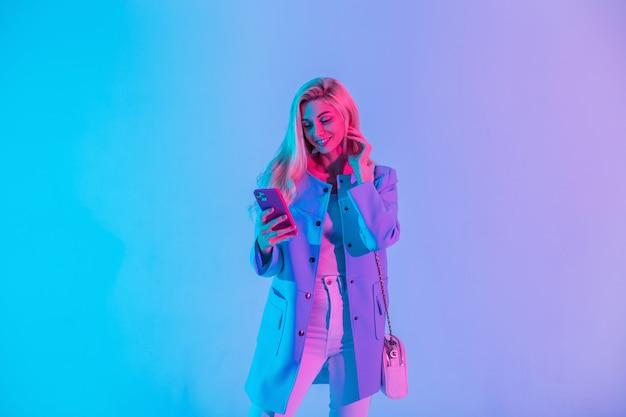 La bella giovane donna felice in un vestito di affari alla moda luminoso guarda con una borsa alla moda tiene un telefono e usa un'applicazione mobile in studio su una luce rosa neon colorata
