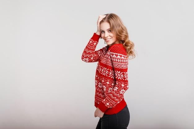Bella giovane donna felice in un maglione rosso vintage di moda su uno sfondo grigio in studio