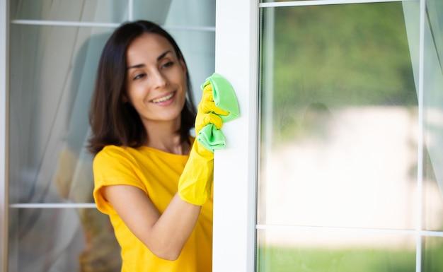 La bella giovane donna felice sta usando uno spolverino e uno spray mentre pulisce una finestra della casa