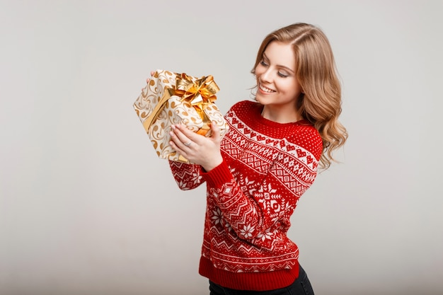 La bella giovane donna felice in un maglione lavorato a maglia rosso tiene un regalo su uno sfondo grigio