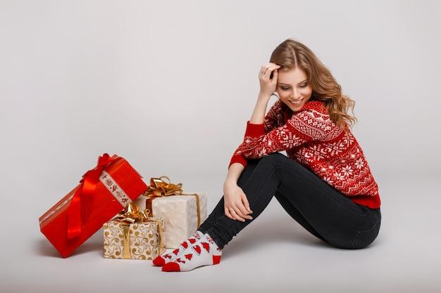 Bella giovane donna felice in un maglione vintage si siede vicino a regali su uno sfondo grigio