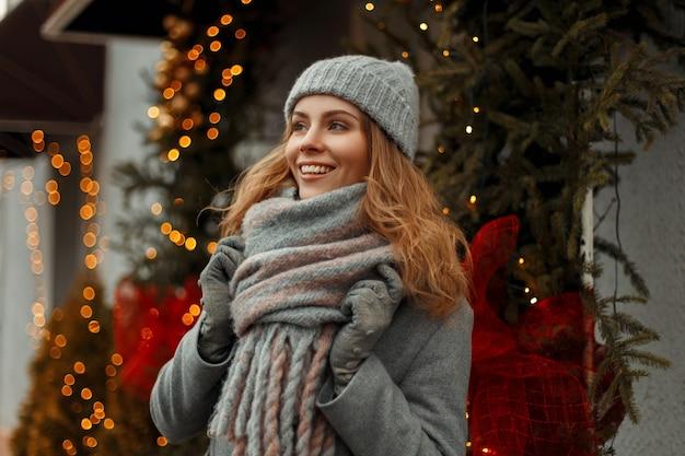 Bella giovane donna felice con un sorriso magico in vestiti di maglieria di moda in un cappello grigio lavorato a maglia e cappotto con un'elegante sciarpa sulla strada vicino alle luci e ghirlande di natale