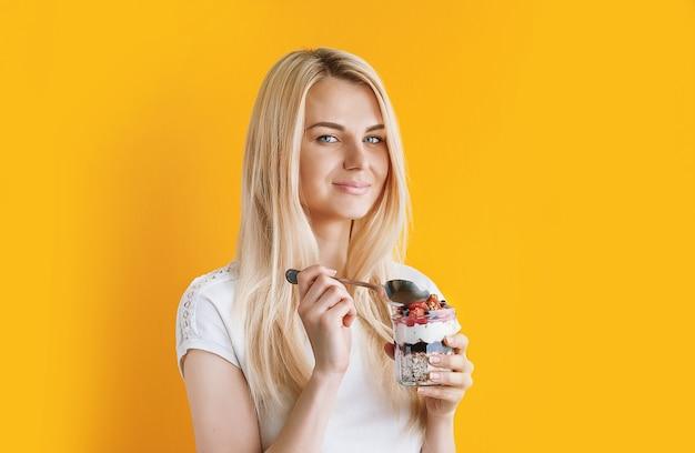 Bella ragazza in buona salute su sfondo luminoso e soleggiato con barattoli in mano. in vasetti porridge di farina d'avena e muesli con frutta bacche e cereali