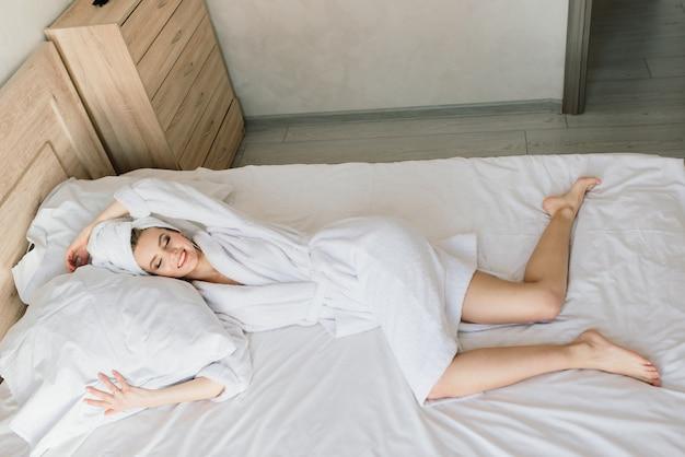 Bella giovane donna in buona salute che si rilassa in una veste, hotes, camera e salone della stazione termale