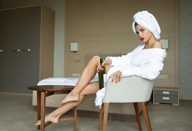 Bella giovane donna in buona salute che si rilassa in una veste.