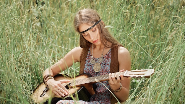 Bella giovane donna del hippie che gioca chitarra che si siede sull'erba