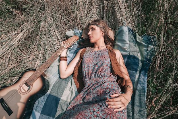 Bella giovane donna del hippie con la chitarra che si trova sull'erba