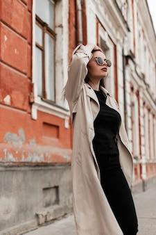 Bella giovane donna giovane hipster in occhiali da sole alla moda in trench vintage cammina vicino al vecchio edificio in città. bella modella bellissima ragazza in capispalla casual alla moda posa per strada in primavera.