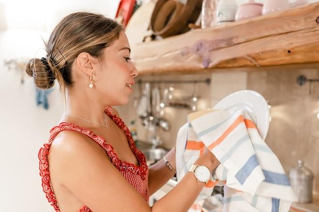 Bella giovane moglie ispanica con un tipico vestito carino che lava e asciuga i piatti dopo la festa a casa