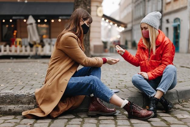 Belle giovani donne in abiti caldi seduti in una strada cittadina e utilizzando disinfettante. belle donne che indossano maschere protettive mentre trascorrono del tempo insieme.