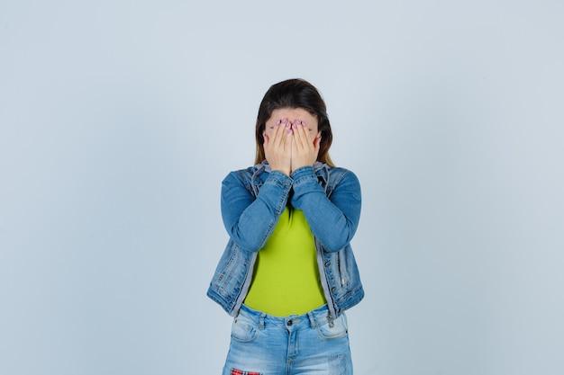 Bella giovane donna che copre il viso con le mani in abito di jeans e sembra offesa, vista frontale.