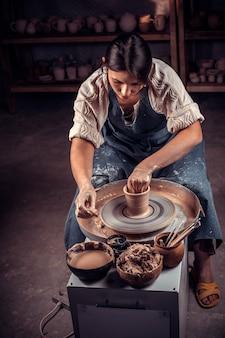 Bella giovane signora che fa ceramiche, scultore di argilla bagnata sulla ruota. produzione artigianale.