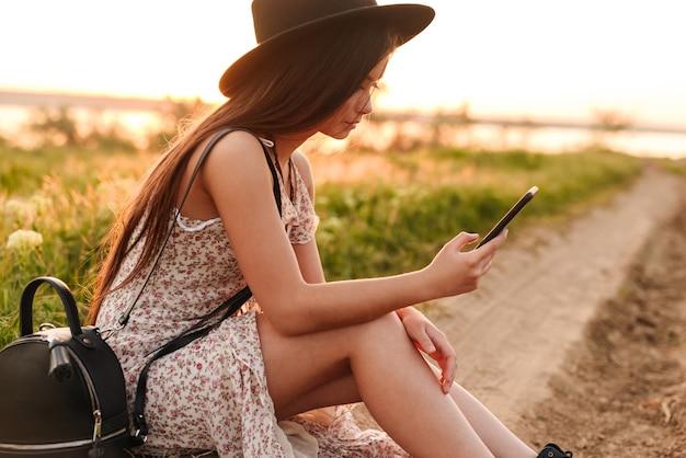 Bella giovane signora che per mezzo del telefono cellulare che porta il cappello.