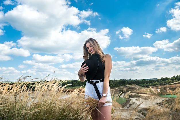 Bella giovane donna che cammina sul campo e rilassarsi durante le vacanze estive