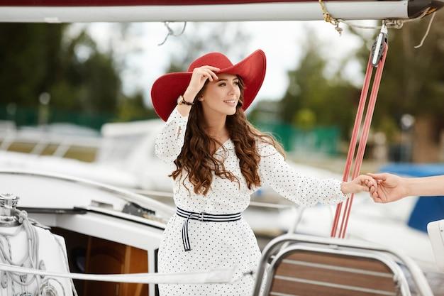 Bella giovane donna in abito bianco e cappello rosso sul ponte di uno yacht in una giornata estiva