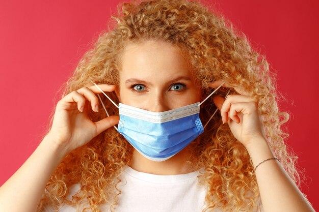 Bella giovane donna con i capelli ricci che indossa la maschera facciale medica si chiuda