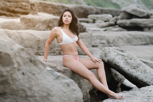 Bella giovane donna latina con lunghi capelli neri che prende felicemente il sole su alcune rocce in spiaggia