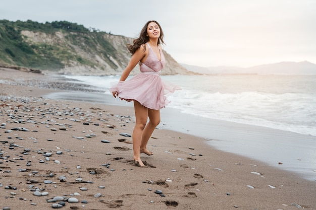 Bella giovane donna latina con lunghi capelli neri, che corre lungo il bordo di una spiaggia al tramonto, con indosso un elegante abito rosa