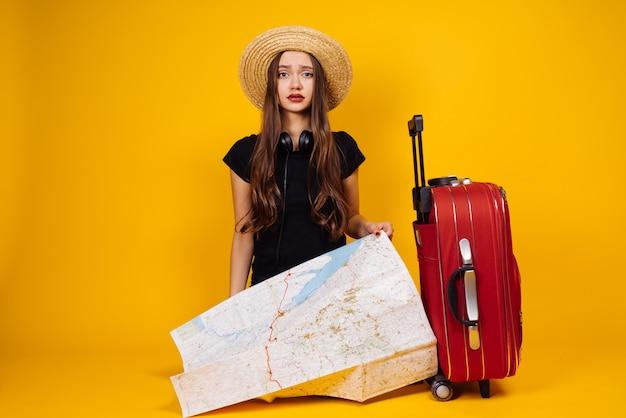 La bella ragazza dai capelli lunghi con un cappello è andata in viaggio con una valigia e una carta