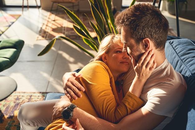 Bella giovane donna sposata caucasica amorevole che guarda con affetto il marito addormentato sul divano