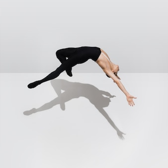 Bello giovane atleta maschio che pratica sul fondo bianco dello studio con le ombre nel salto, volo dell'aria