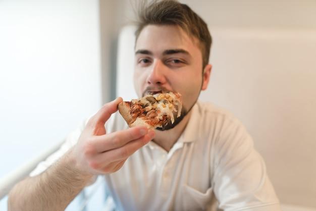 Un bel giovane mangia una pizza appetitosa e guarda la telecamera. un ragazzo con la barba serve un pezzo di pizza.