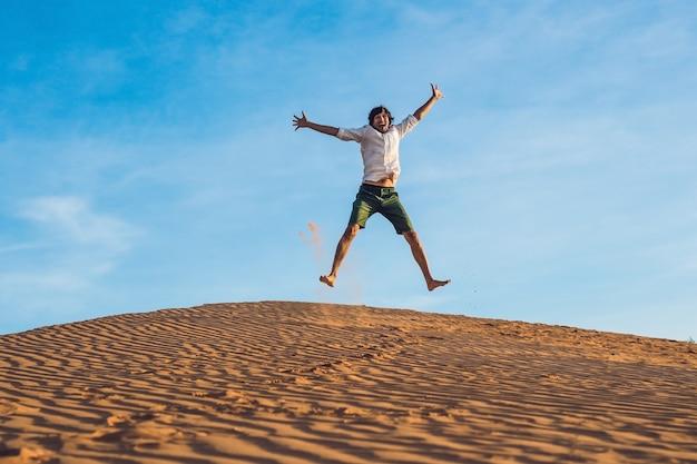 Bello giovane che salta a piedi nudi sulla sabbia nel deserto godersi la natura e il sole. divertimento, gioia e libertà.