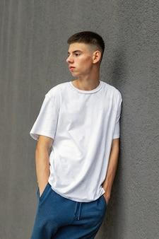Bel giovane appoggiato al muro di cemento, stile di vita, tendenze giovanili, argomenti lgbt, orgoglio