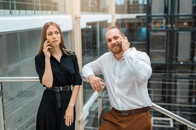 Bella giovane uomo e donna in un business center a parlare al telefono