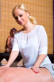 Una bella giovane massaggiatrice che applica un massaggio a un cliente maschio in uno studio.